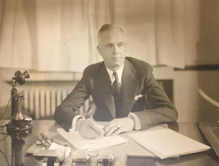Ewert, in a suit, sits at his desk, holding a pen as if he's about to begin writing. Papers and a telephone are visible on his desk. Sepia photograph.