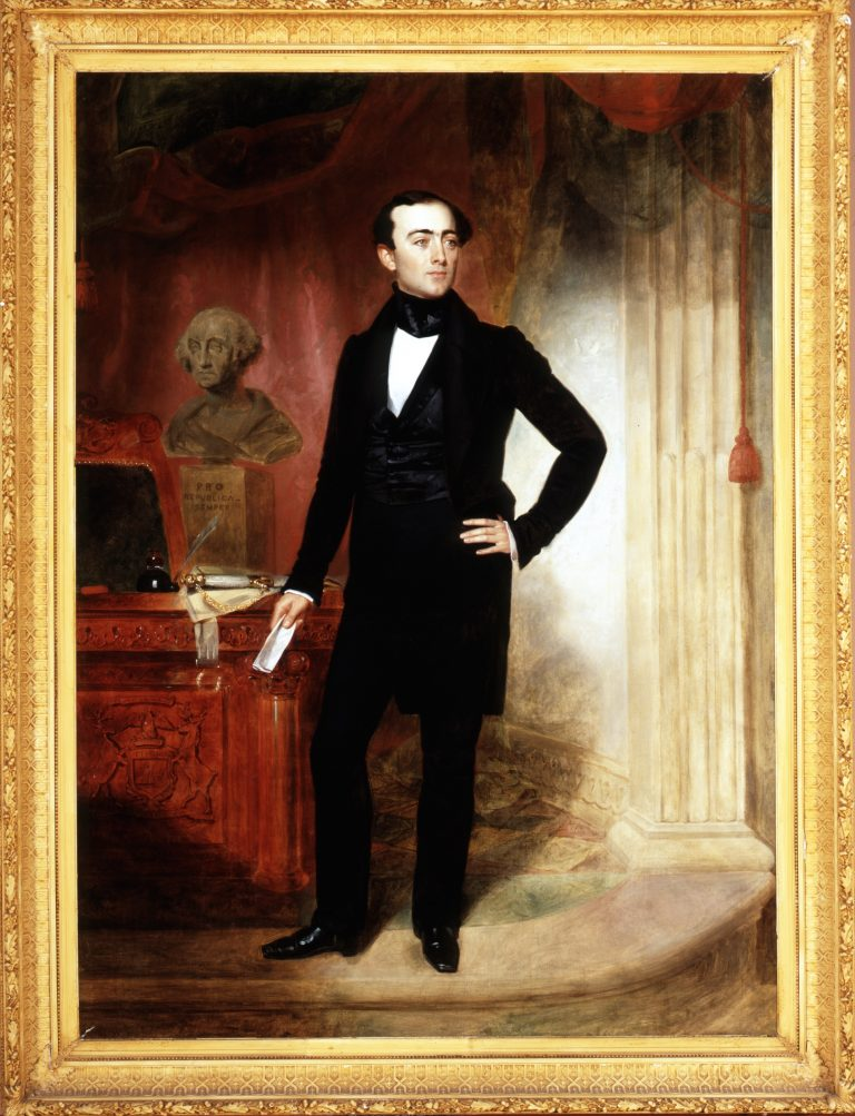 Official painting of Stevens T. Mason as governor of Michigan. He is standing beside a desk with Michigan's coat of arms on the front of it.