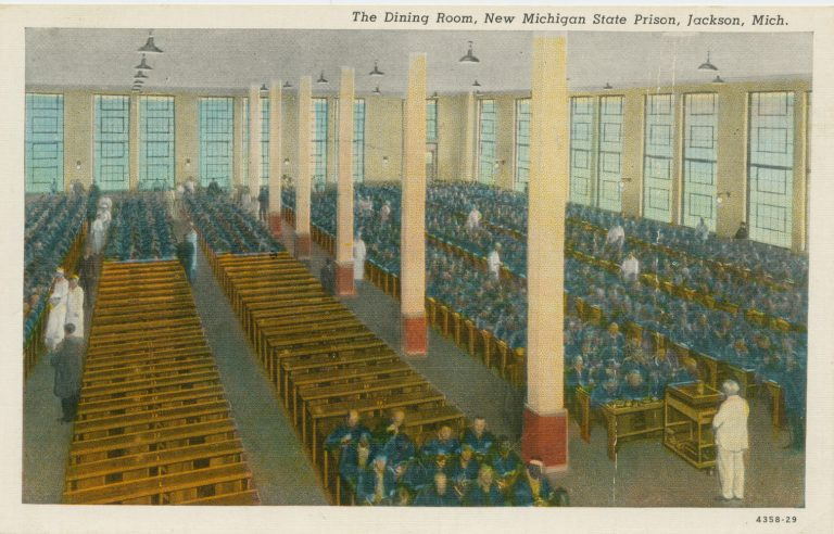 Illustration of an dining room at Jackson Prison with rows of narrow tables, some of which have rows of men in blue suits sitting at them.