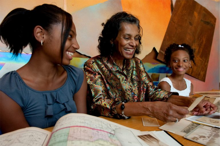 Adult woman and two young girls smile and laugh while paging through historic documents laid out on a wood table.