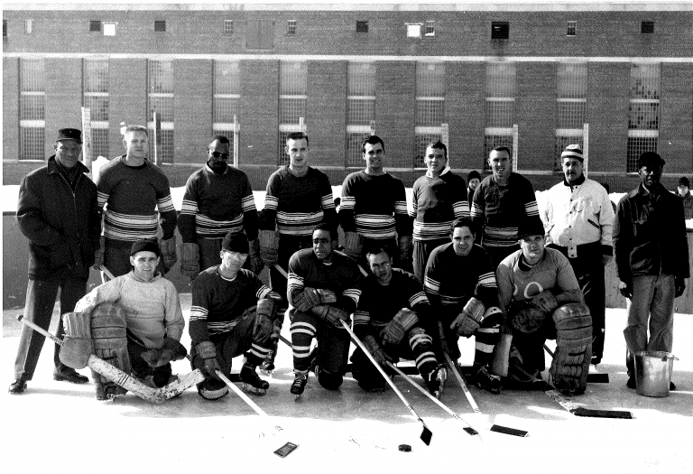 15 men, most of whom are wearing striped hockey jerseys, stand in two rows and pose with their hockey sticks for a group photo