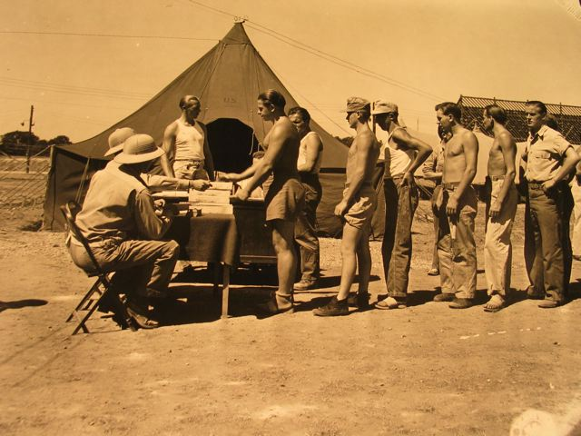 7 men, some without shirts, line up in front of a table at which two men in hats are seated. A tent is visible in the background.