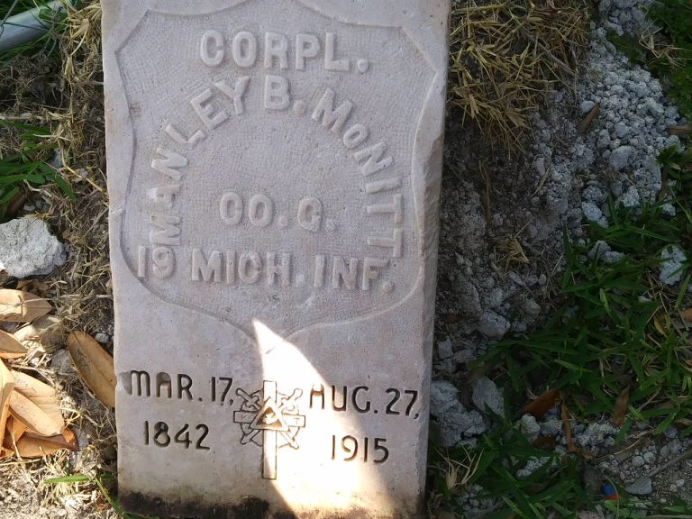 A square, flat tombstone with the name Corpl. Manley B. McNitt and the dates March 17 1842-Aug 27 1915