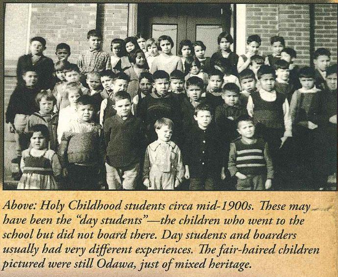 "Black and white photo of approximately 40 young students posing for a group photo on the steps of a brick building. Embedded caption reads: ""These may have been the 'day students' - the children who went to the school but did not board there. Day students and boarders usually had very different experiences. The fair-haired children pictured were still Odawa, just of mixed heritage."""