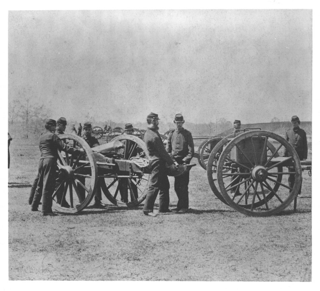 Two soldiers are loading a cannon while four soldiers cluster around another cannon.