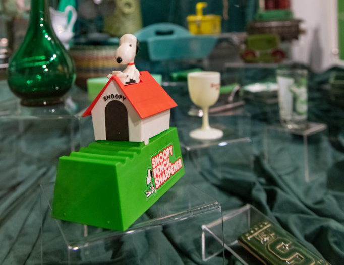 Museum exhibit featuring a wide area of artifacts that are green. A green Snoopy Pencil Sharpener is visible in the foreground.