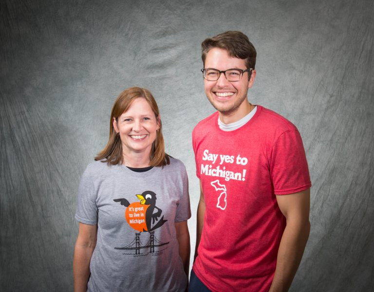 A man and woman posing for a photo - each wearing a t-shirt with a Michigan Tourism slogan on it.
