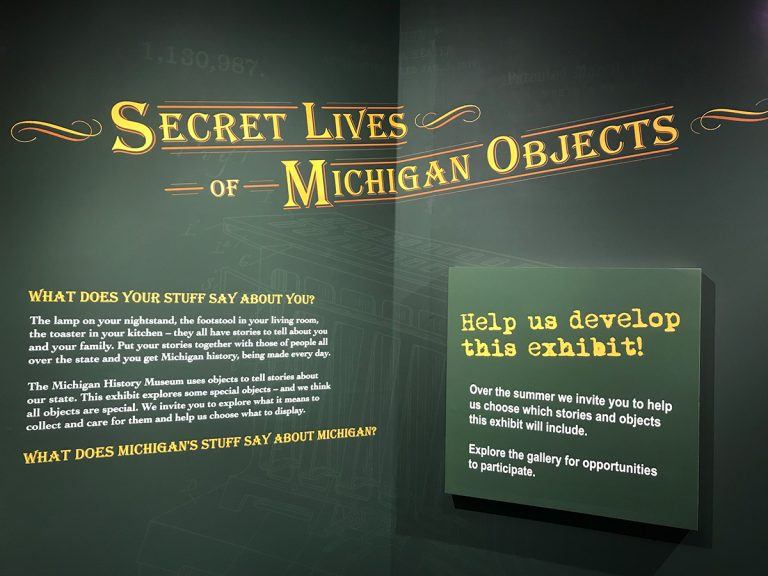 "Green wall with ornate title ""Secret Lives of Michigan Objects"" in yellow script."