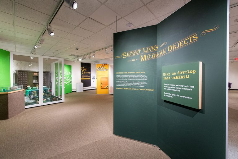 Wide shot of the Secret Lives of Michigan Objects exhibit space with a large green introduction label in the foreground.