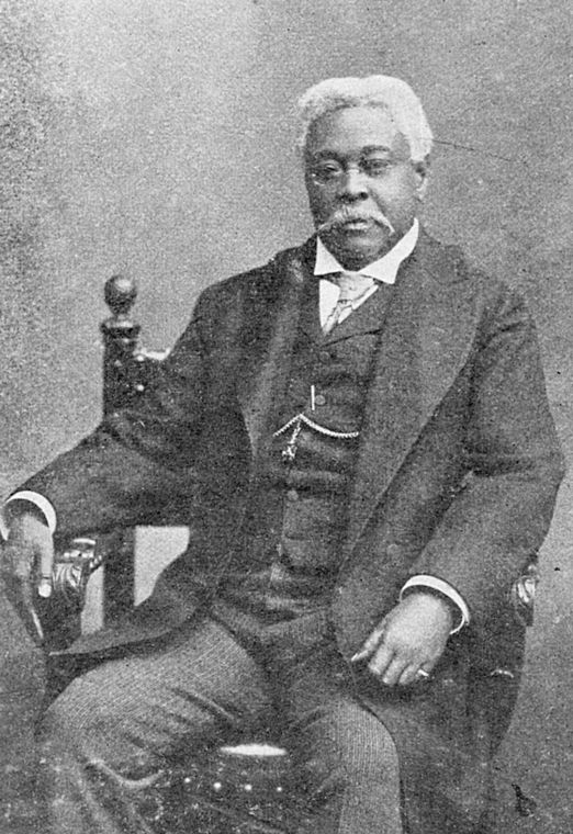 A studio photograph of David Augustus Straker sitting in a chair.