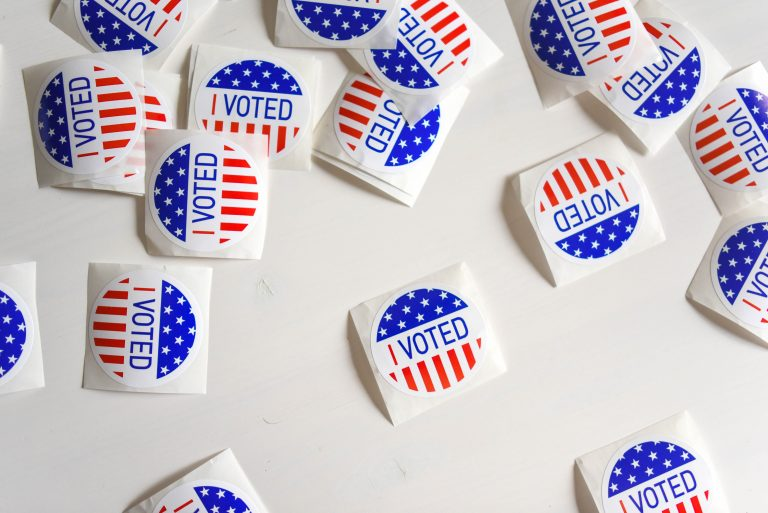 "White stickers reading ""I Voted"" scattered on a white background"