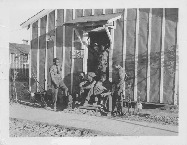 5 men in CCC uniform lounge on the steps outside a barracks.